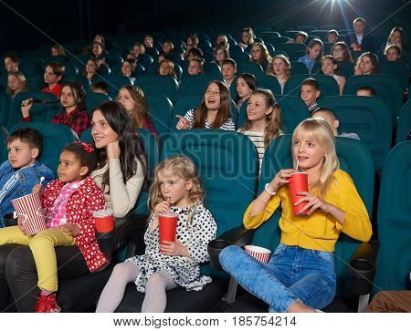 Cinema hall full of children and their parent enjoying movie premiere together entertainment activity hobby lifestyle people emotions excitement amusement expressive concept.