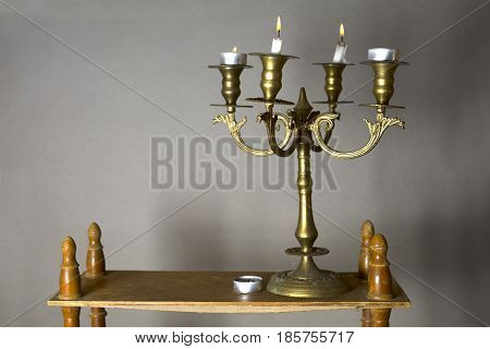 Burning candles in a retro bronze candle holder placed on wooden shelf