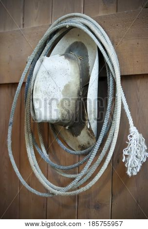 An Old Sweat Stained Cowboy Hat and Frayed Rope Lariat Hanging on a Wood Panel Wall