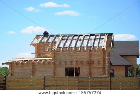 Roofing Construction. Roofer Contractor. Builder repair and lay asphalt shingles roof shingles on wooden house roof. Roofer Install Asphalt Roof Shingles. roof repair. poster