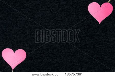 Dark heart background with free empty blank copy space for text or quote. Two red classic love shapes cut from cardboard or paper on wooden sticks in the corner. Gray or black texture backdrop.
