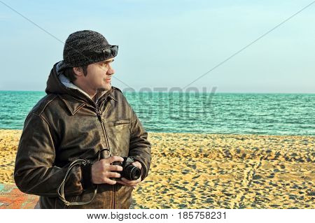 Photographer with retro photo camera on sunny sea beach.