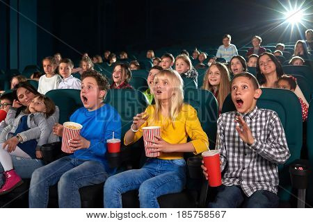 Young boys and girls looking shocked and surprised watching a movie at the cinema emotions expression shock surprise unexpected action activity entertainment people leisure hobby lifestyle concept.