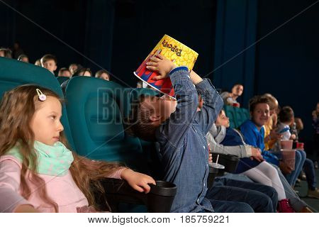 Little greedy boy eating popcorn from a big bucket during movie premiere at the cinema people children kids childhood snack food delight entertainment fun happiness concept.