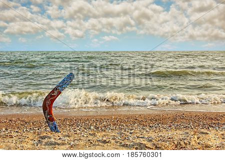 Multicolored Australian Boomerang on sandy beach against of sea surf and dramatic sky.Toned image.