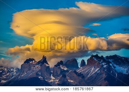 Cumulus clouds in the rays of the sunset. The cliffs of Los Cuernos is covered with snow and ice. The concept of extreme and active tourism. Torres del Paine National Park