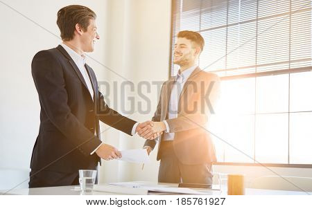 Two business people shaking hands in office as sign of partnership