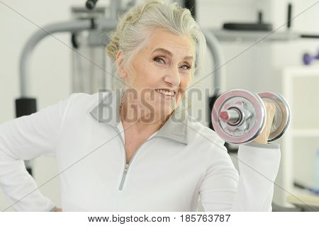 Portrait of a beautiful  elderly woman in a gym with dumbbells