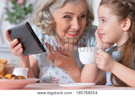 Grandmother with little granddaughter playing in a tablet computer
