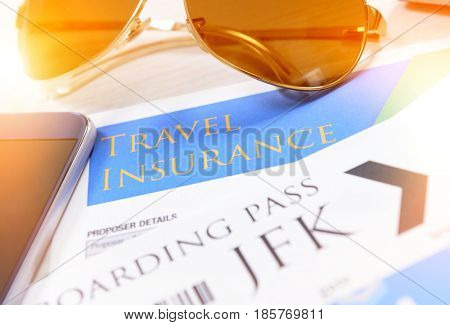 Airline boarding pass tickets with travel insurance,  sunglasses, mobile phone