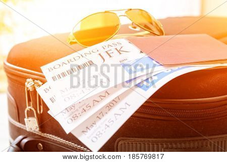 Airline boarding pass tickets with passport and sunglasses on a luggage