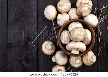 Fresh white mushrooms champignon in brown bowl on dark wooden background. Top view. Copy space.