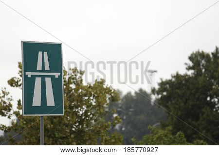 Green highway traffic sign in front of trees in park.
