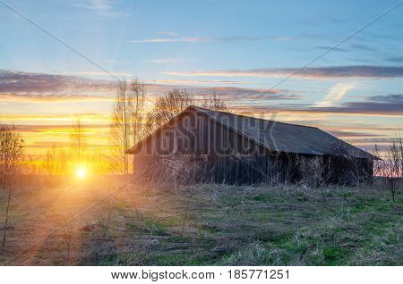 Old Barn On A Hill And The Sunset In A Rural Village Location.