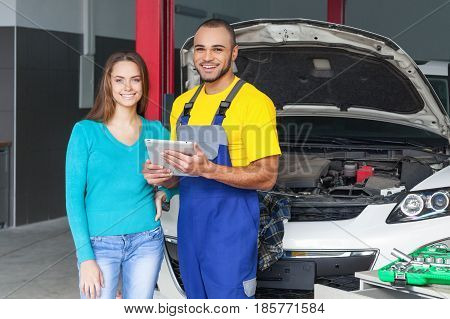 Auto Mechanic and Customer Smiling in Auto Repair Shop