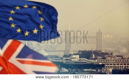 The European Union and the British Union flag over aerial view of London with financial symbols of London in the background - Brexit concept
