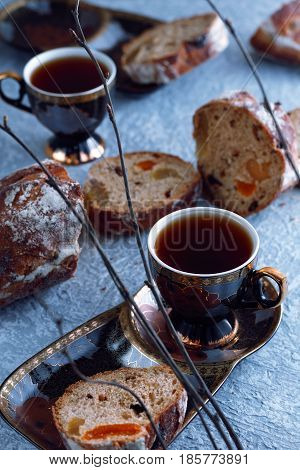 Close-up of afternoon tea for two persons with black tea and sweet bread with dried apricots, raisins and figs. Blue background for springtime, decoration of twigs.