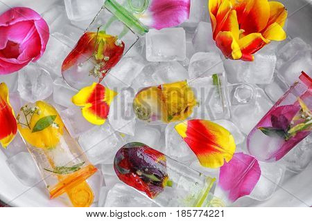 Homemade popsicles with flowers on ice cubes