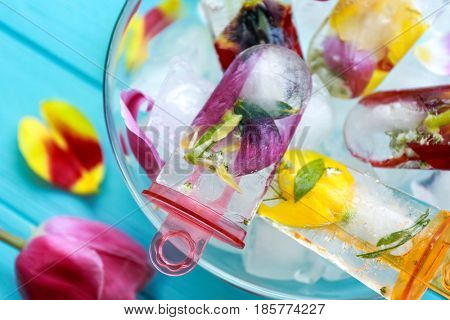 Homemade popsicles with flowers in glass bowl on blue wooden table
