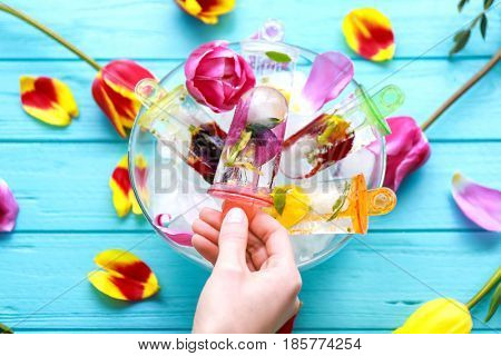 Female hand taking popsicle out of glass bowl on wooden table