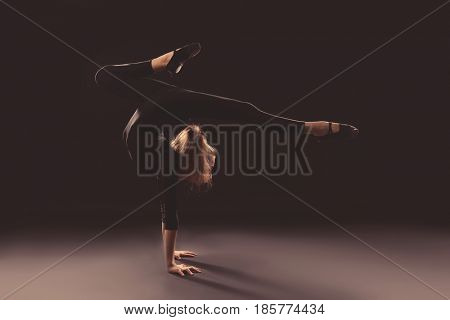 Young girl doing gymnastics on dark background