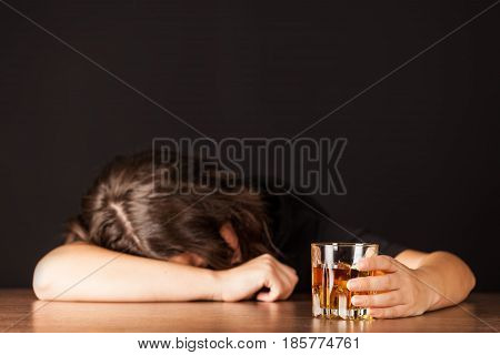 Drunk Woman Sleeping At Bar Counter Holding a Glass of Whisky