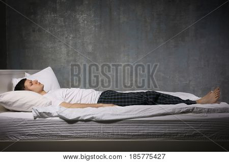 Young man sleeping in bed