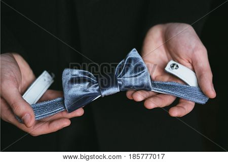 A man holds a blue velvet bow tie in his hand on a black background