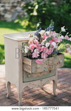 A vintage beige bedside table stands outside in the summer, decorated with a bouquet of pink roses flowers