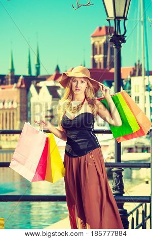 Spending money on sales buying things concept. Fashionable woman relaxing and standing with shopping bags in town wearing glamorous outfit and big sun hat
