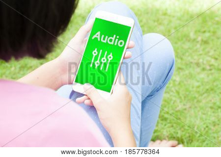 Top view of woman using her mobile phone with multimedia music broadcast technology concept.