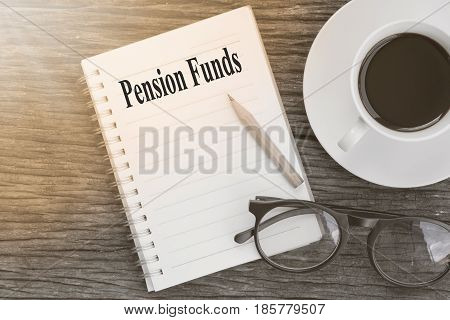Concept Pension Funds message on notebook with glasses pencil and coffee cup on wooden table.