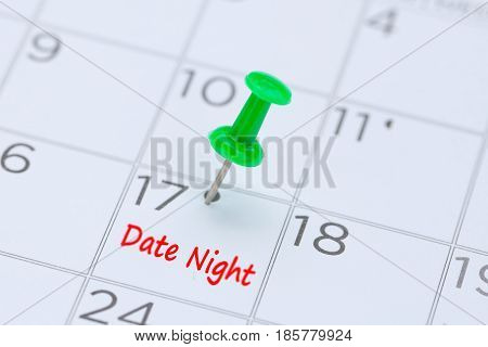 Date Night written on a calendar with a green push pin to remind you and important appointment.