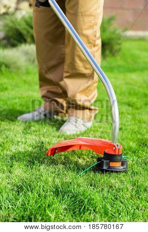 Closeup of a Gardener Using a Weed Trimmer