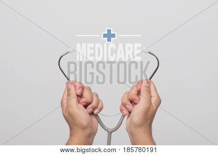 Hands holding a stethoscope and word