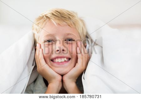 Portrait of smiling boy lying under bed sheet in bedroom at home