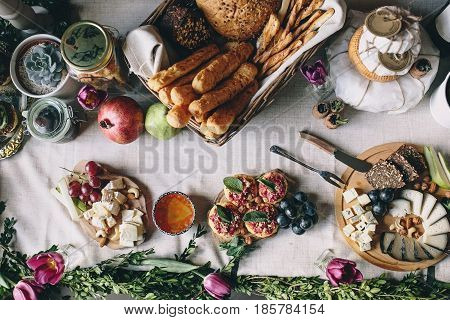 Picnic table: sliced goat cheese, dorblu, bread, grapes, pear, hazelnuts, cashew on a wooden plate, wicker basket with bread, snacks from crackers and beets, honey and pomegranate