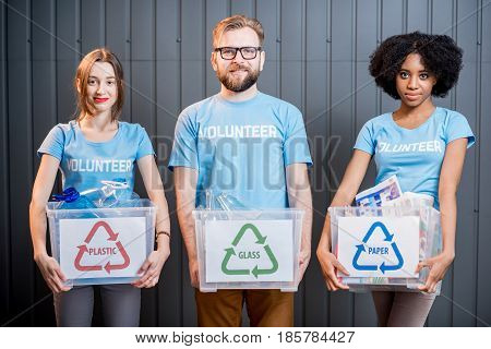 Portrait of three multi ethnic volunteers holding containers with sorted waste standing indoors