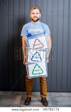 Male volunteer in blue t-shirt holding containers with sorted waste standing indoors on the gray wall background. Focused on the containers