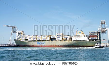 Oakland CA - May 09 2017: Cargo Ships are unable to maneuver sideways. Tugboats LIBERTY and PATRIOT push cargo ship KAUAI sideways to the dock at the Port of Oakland.