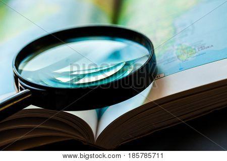 Closeup of a Magnifying Glass on an Atlas