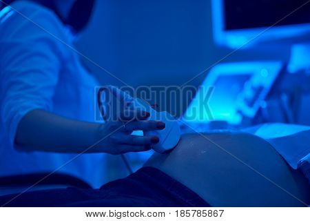 Doctor performing ultrasound scanning for her pregnant patient pregnancy healthcare professionalism experience health diagnostic sonogram concept.
