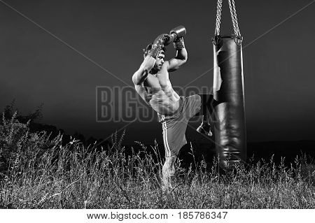 Black and white shot of a kick boxer training on a heavy bag outdoors kicking it with his knee copyspace kickboxing martial arts combat fighting practicing performance concentration determination.