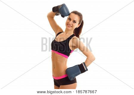 a young athletic girl stands in boxing gloves black top and shorts and smiling isolated on white background