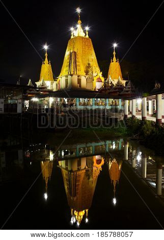 Beautiful night view of the Ye Kyaung Buddhist Temple reflecting in the water Hpa-An city Myanmar.