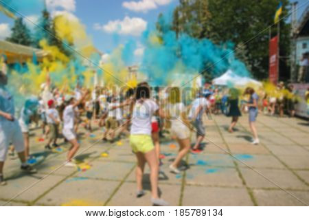 happy people crowd partying under colorful powder cloud at holi fest festival of colors in summer amazing moment
