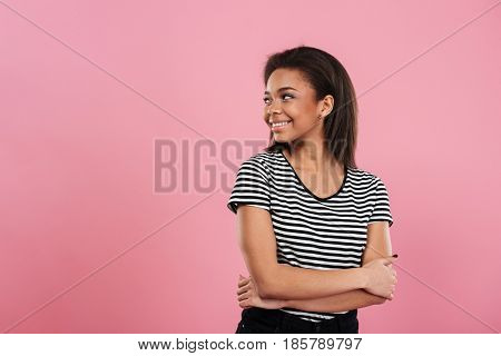 Portrait of a pretty smiling african girl looking away and standing with her arms folded isolated over pink background