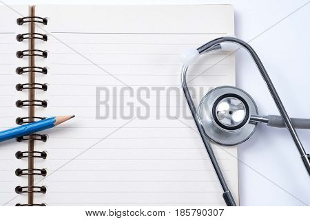 Medical concept : stethoscope on note book and pencil with white background