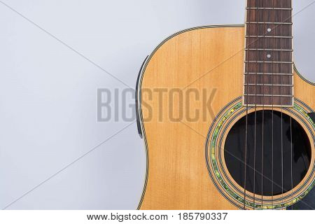 Close up acoustic guitar on gray background