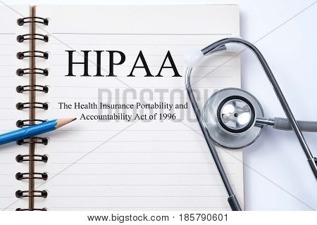 Notebook and pencil with HIPAA (The Health Insurance Portability and Accountability Act of 1996) on the table with stethoscope medical concept